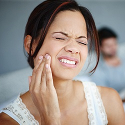 Grimacing woman holding jaw in pain